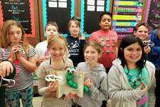 Students from Laura Brown's reading enrichment class proudly show off the ornaments that they created for their entry to the Festival of Trees. Students did the project to utilize a variety of educational skills for their class. (Courtesy photo)