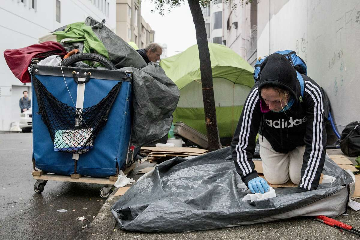 Bonnie Lukesh works to clean off her tent before packing it up with her other belongings during a sweep of homeless tents and encampments by the Department of Public Works and San Francisco Police along Willow Street in San Francisco, Calif. Wednesday, Dec. 4, 2019.