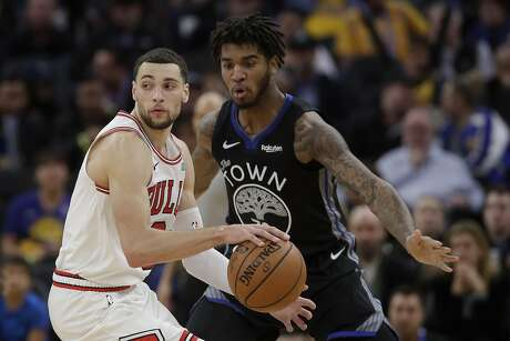 Chicago Bulls guard Zach LaVine, left, dribbles against Golden State Warriors forward Marquese Chriss during an NBA basketball game in San Francisco, Wednesday, Nov. 27, 2019. (AP Photo/Jeff Chiu)