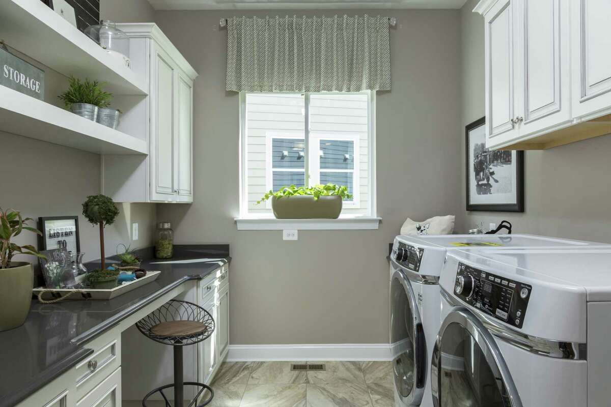 A laundry room in a model home in Lake Frederick, VA, has work space and storage as well as a washer and dryer. (Photo by Benjamin C. Tankersley/For The Washington Post via Getty Images)
