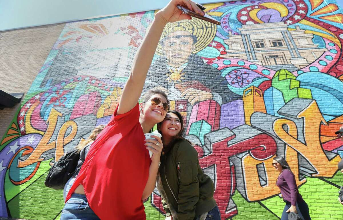 University of St. Thomas students Raiza Torres (left) and Heidi Chang attempt to take a photo in front of Gonzo247's first on-campus mural Thursday, March 21, 2019, in Houston. The large mural was painted by well-known graffiti artist Mario Figueroa, Jr., who goes by the moniker Gonzo247, depicts St. Thomas Aquinas, the Italian Catholic priest who inspired the university's name.