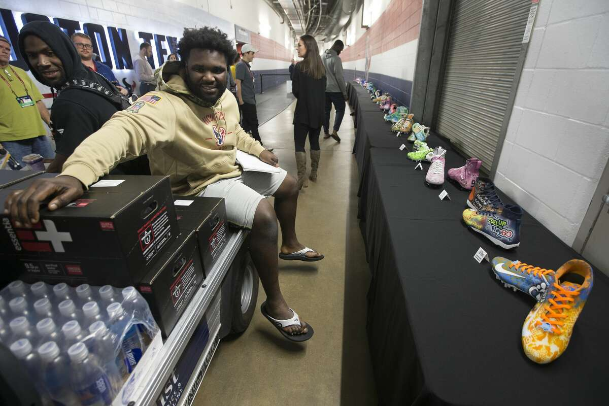 Texans tackle end D.J. Reader rides past the lineup of the Texans players' My Cause, My Cleats display. Reader's cleats highlight the National Kidney Foundation and Fuel up to Play 60. His father died of kidney disease in 2013.