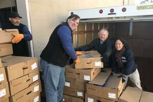 Two unidentified volunteers from a local food pantry pick up an order at Connecticut Food Bank's Bridgeport warehouse. Shown at far left loading up the truck is Rafael Davis, a Warehouse Specialis for the food band and to his right is Jim Stuhlman, manager of the Bridgeport warehouse.