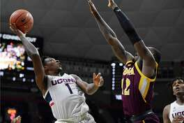 UConn's Christian Vital, left, shoots over Iona's Tajuan Agee on Wednesday in Storrs.