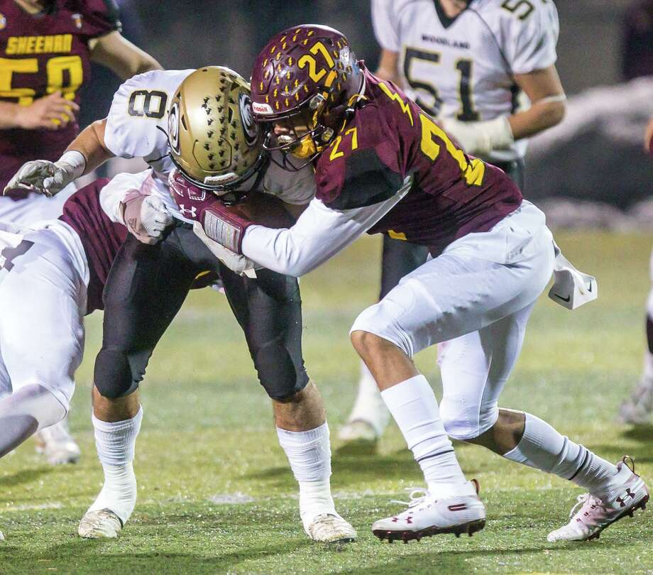Woodland's Jason Palmieri battles for yards against Sheehan's Jordan Davis during their Class S quarterfinal game on Wednesday. Photo: John Vanacore / For Hearst Connecicut Media / (C)John H.Vanacore