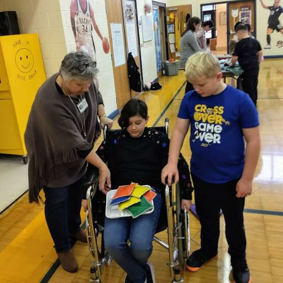 Special education teacher Debbie Oppel and student Jake Schneider assist fellow student Sophie Hawksley maneuver a wheelchair while carrying a lunch tray. Photo: Contributed Photo / Connecticut Post