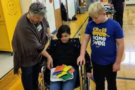Special education teacher Debbie Oppel and student Jake Schneider assist fellow student Sophie Hawksley maneuver a wheelchair while carrying a lunch tray.