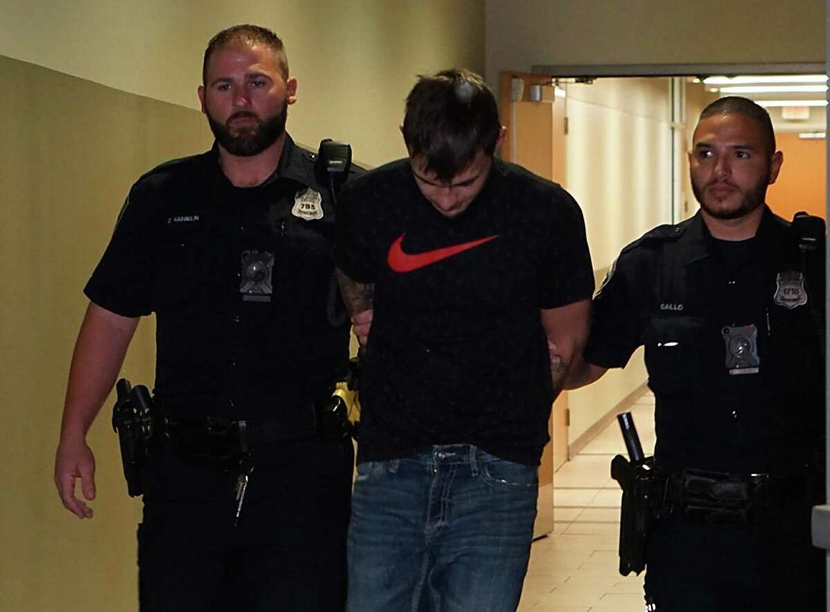 Jason Daniel Davis, 23, is escorted by police to a waiting vehicle to be transported to the Bexar County Jail. He's accused of murder in the death of 26-year-old Frank Lara Jr., whose body was discovered Aug. 24, after he had been missing for a month.