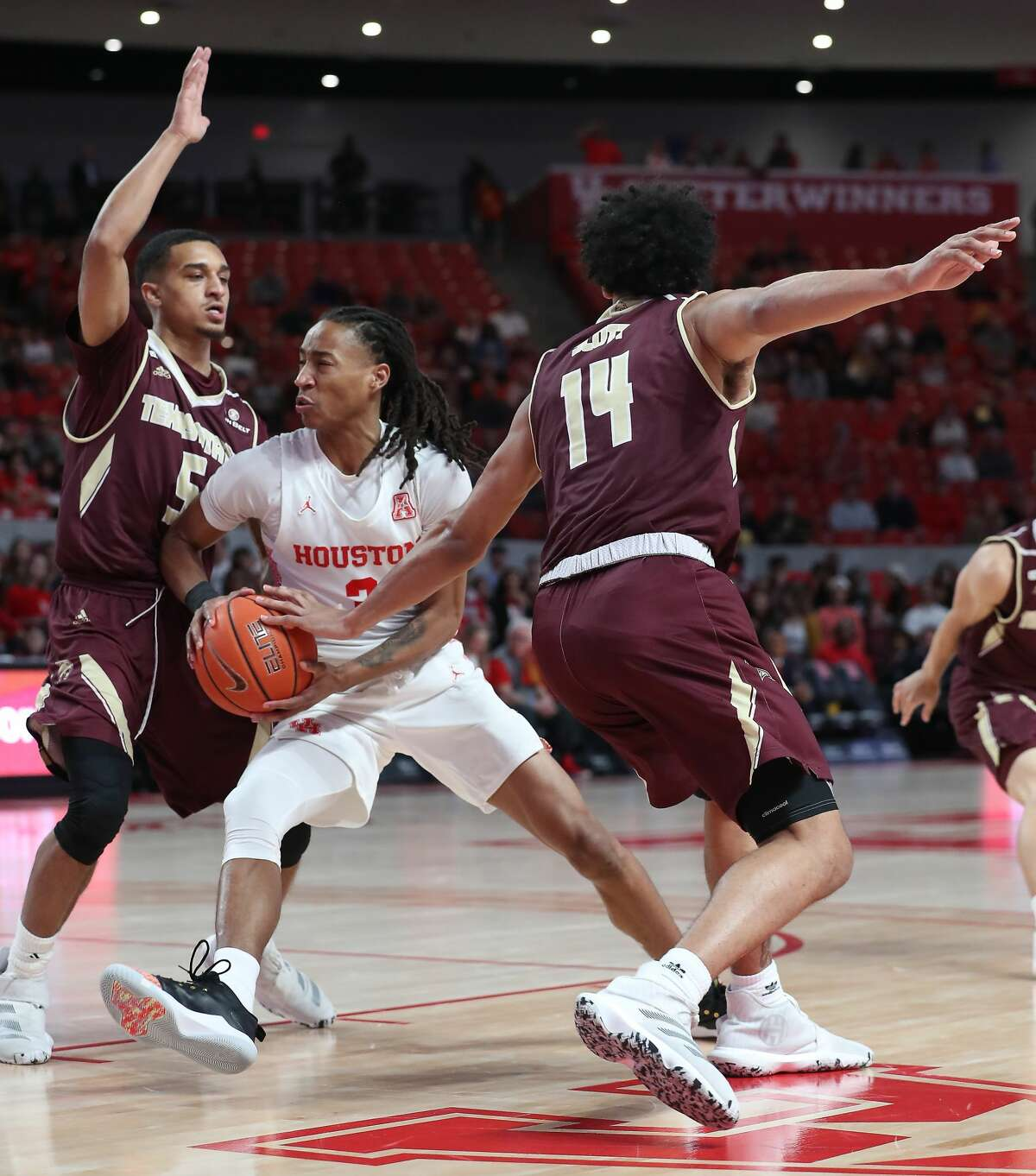 Houston Cougars guard Caleb Mills (2) drives pass Texas State Bobcats guard Marlin Davis (5) and forward Quentin Scott (14) during the first half of an NCAA basketball game at Fertitta Center Wednesday, Dec. 4, 2019, in Houston.