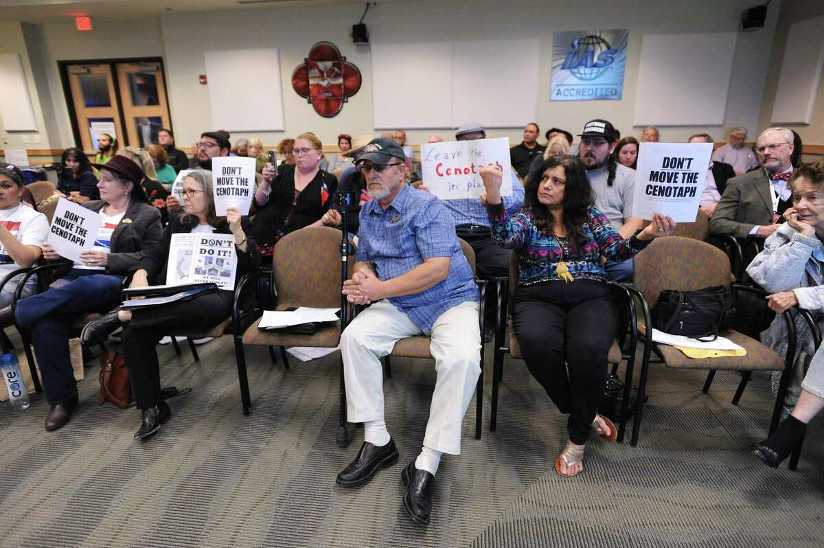 People hold up signs demanding that the Cenotaph at the Alamo not be moved during the Dec. 4 presentation on the first phase of the Alamo project at the city's Historic and Design Review Commission.