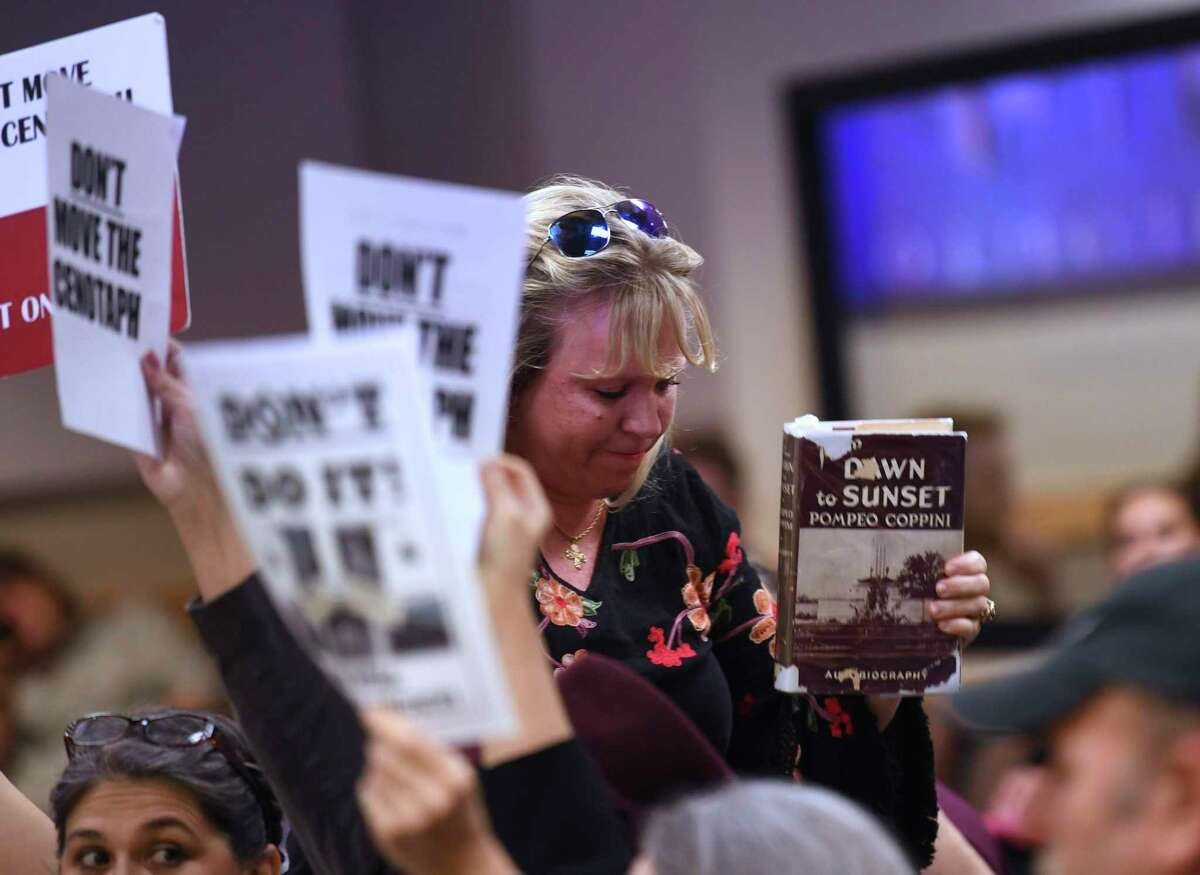 Cindy Gaskill holds up a book about Pompeo Coppini, the Italian artist responsible for the Cenotaph on the Alamo grounds, during the presentation on the first phase of the Alamo project at the city's Historic and Design Review Commission at the Development Service Building on Wednesday, Dec. 4, 2019. Gaskill spoke at the meeting, expressing her concern that moving the Cenotaph would go against the vision of the artist.