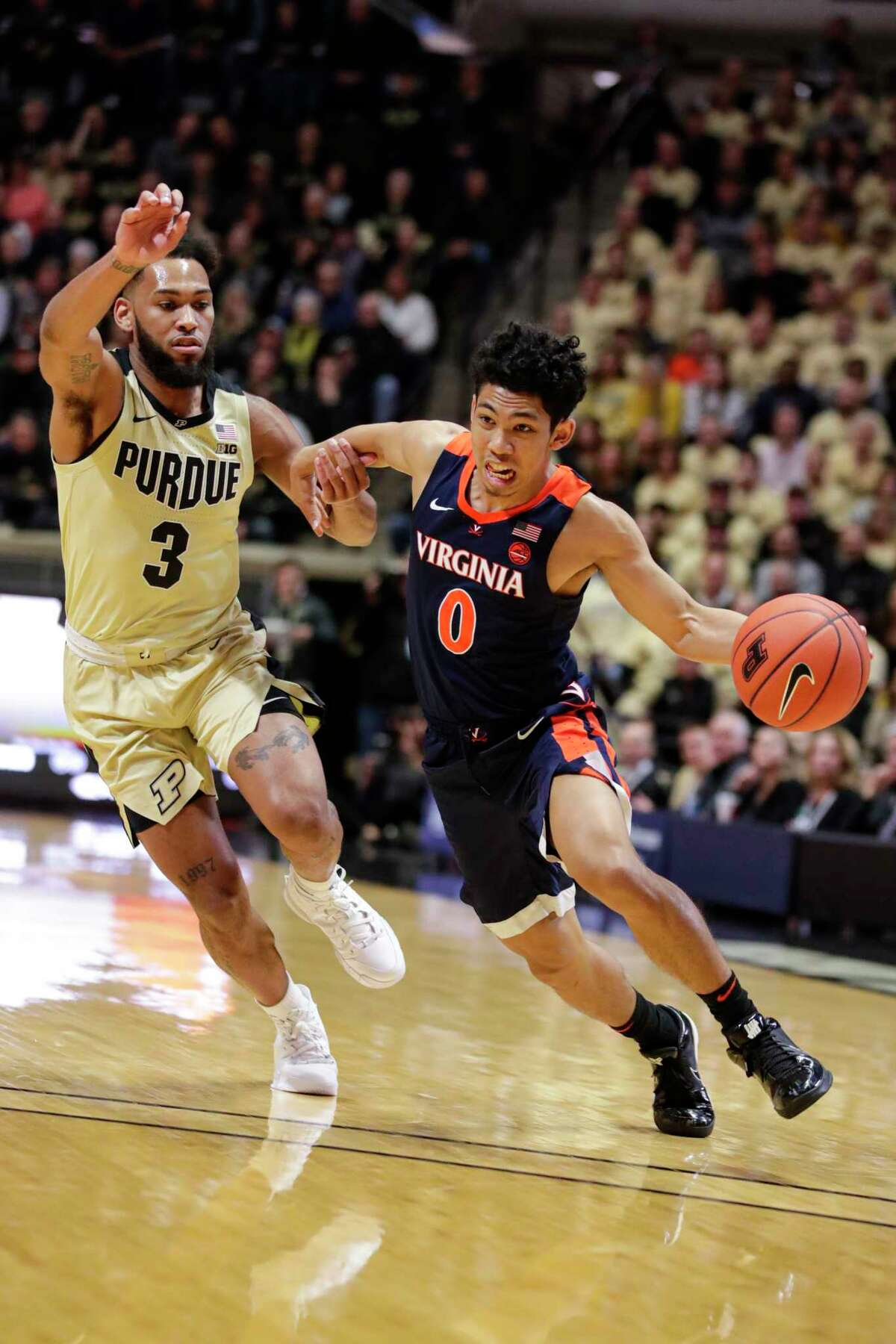 Virginia guard Kihei Clark (0) drives on Purdue guard Jahaad Proctor (3) during the first half of an NCAA college basketball game in West Lafayette, Ind., Wednesday, Dec. 4, 2019. (AP Photo/Michael Conroy)