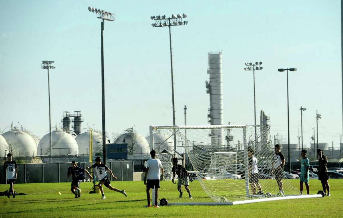 Port Neches - Groves High School students play soccer on the practice field adjacent to the school, where just two days prior crews outfitted in haz-mat gear combed the field for any potential debris from the TPC Group plant explosion. Photo taken Wednesday, December 4, 2019 Kim Brent/The Enterprise
