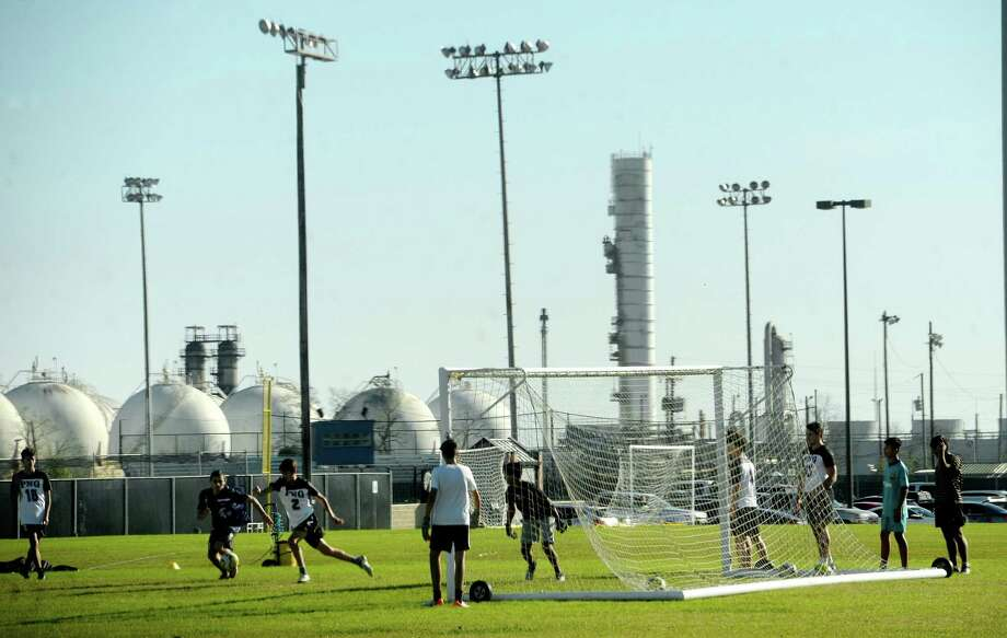 Port Neches - Groves High School students play soccer on the practice field adjacent to the school, where just two days prior crews outfitted in haz-mat gear combed the field for any potential debris from the TPC Group plant explosion. Photo taken Wednesday, December 4, 2019 Kim Brent/The Enterprise Photo: Kim Brent / The Enterprise / BEN