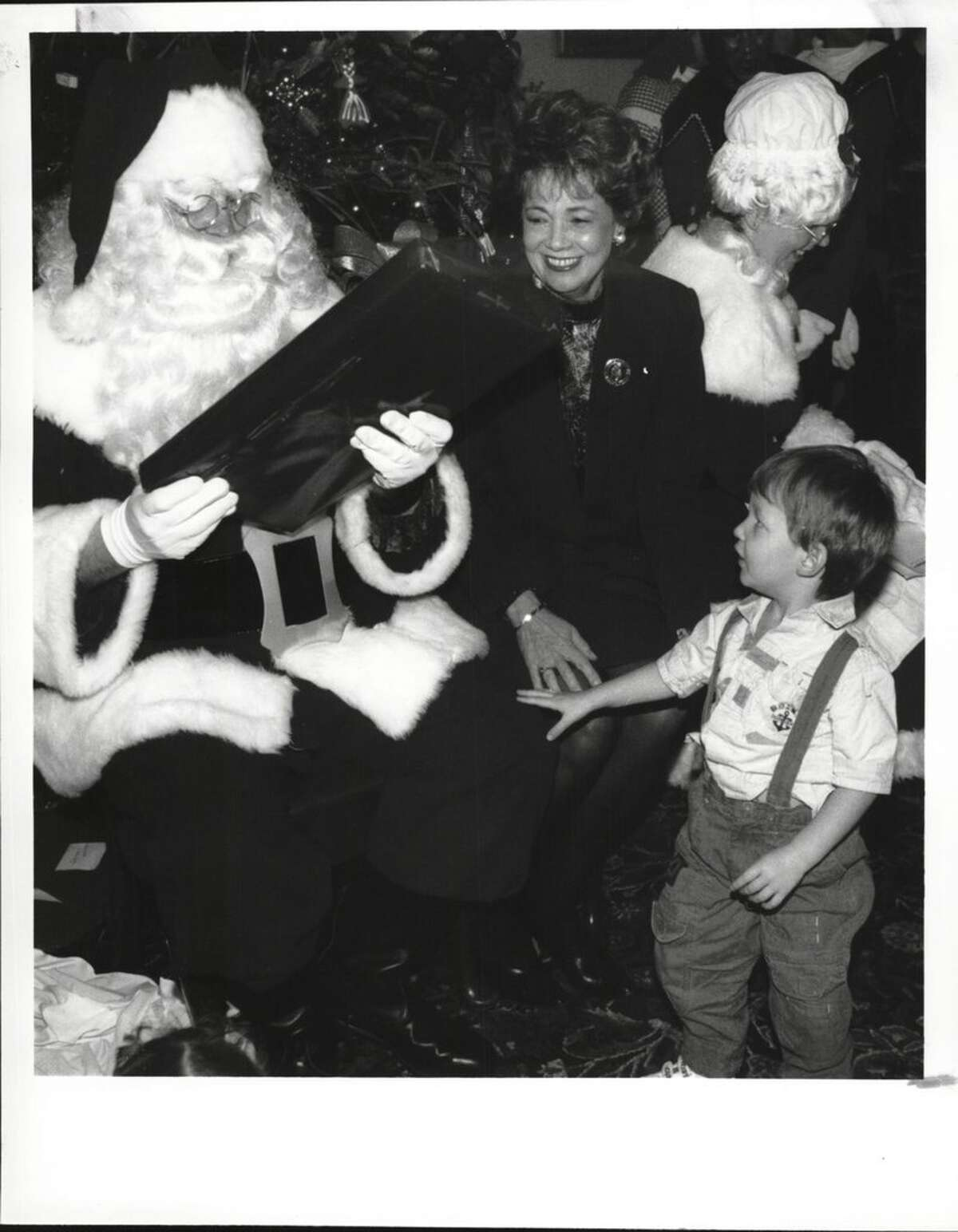 Albany, New York - Santa Claus (Jay North) talks with 2 1/2 year old Andrew Gonyea of Albany from the Albany Girls Club group as Matilda Cuomo watches during her annual Christmas party for kids at the Governor's Mansion. December 18, 1992 (Paul D. Kniskern, Sr./Times Union Archive)