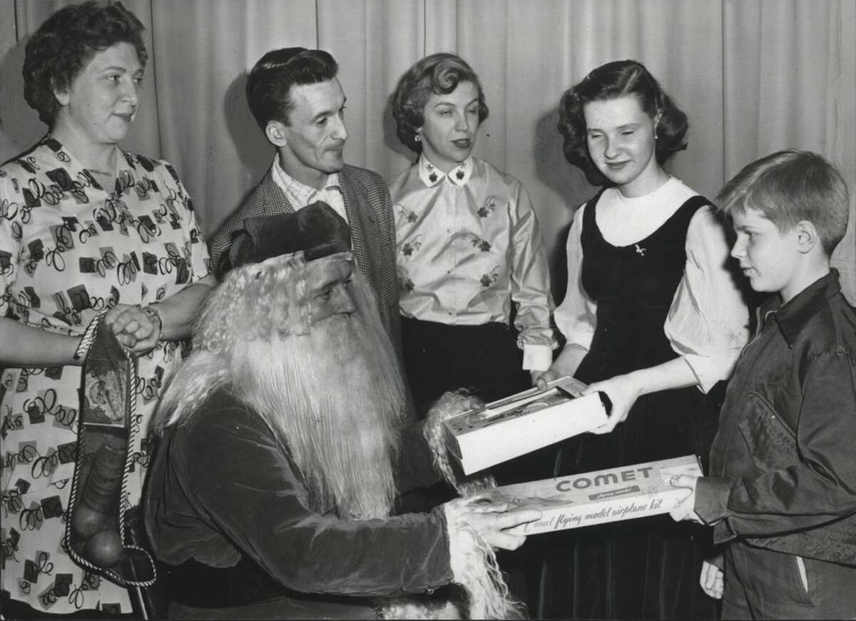 Santa Clause distributed presents yesterday at a party at Scully Post, American Legion, sponsored by the Association for the Help of Retarded Children and the Albany Elks Club. Santa is Elmer Parker, representing the Elks, and the adult helpers, from left, are Mrs. Marie Van Amerongen, co-chairman; Louis Ramundo, whose orchestra played for the party, and Mrs. Rose Alice McGloine Jr. Unidentified boy at the right was a guest at the party. December 30, 1954 (Knickerbocker News Staff Photo/Times Union Archive)