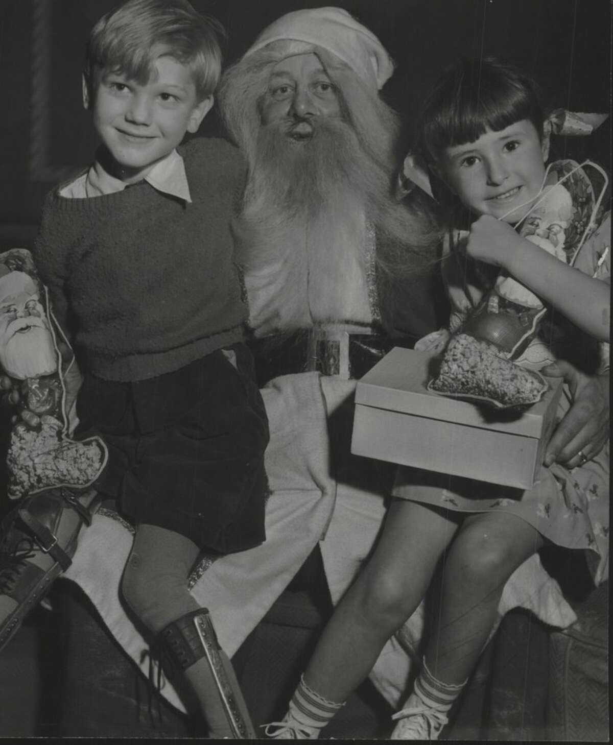 Bobby Dexter and Adrian Allen sit on Santa Claus' lap. December 23, 1943 (Times Union Archive)