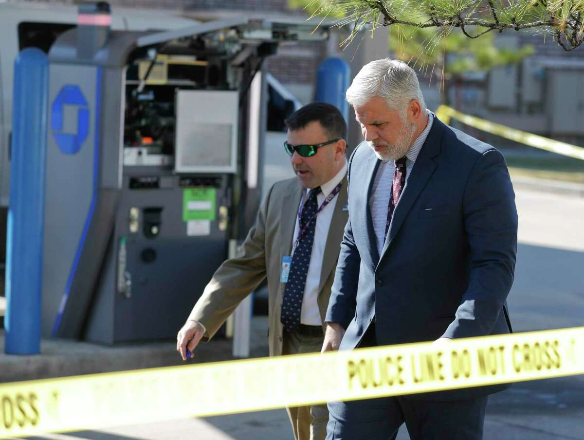 Montgomery County District Attorney Brett Ligon, right, walks the scene with Major Crimes Division Chief Rob Freyer after two men attempted to rob a Brinks security employee while servicing an ATM at a Chase bank, Tuesday, Nov. 19, 2019, in Willis. The employee shot and killed one suspect, while law enforcement is searching for the other who fled.