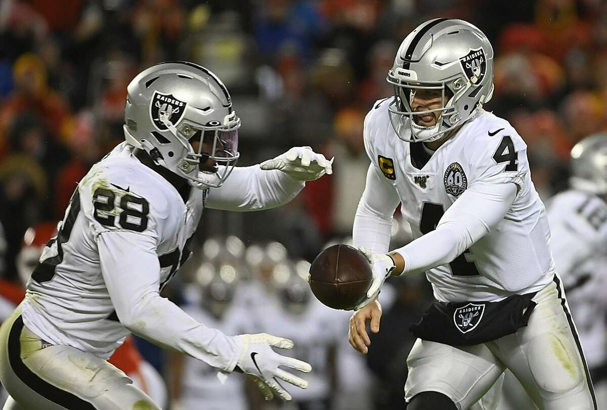 Oakland Raiders quarterback Derek Carr (4) hands off to Oakland Raiders running back Josh Jacobs (28) during the second half of an NFL football game against the Kansas City Chiefs in Kansas City, Mo., Sunday, Dec. 1, 2019. (AP Photo/Reed Hoffmann)