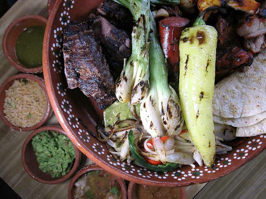 Parrillada al Carbon for two includes steak, chicken, shrimp, sausage, quesadillas, peppers, onions, rice, beans and guacamole at Tlahco Mexican Kitchen. Photo: Mike Sutter /Staff