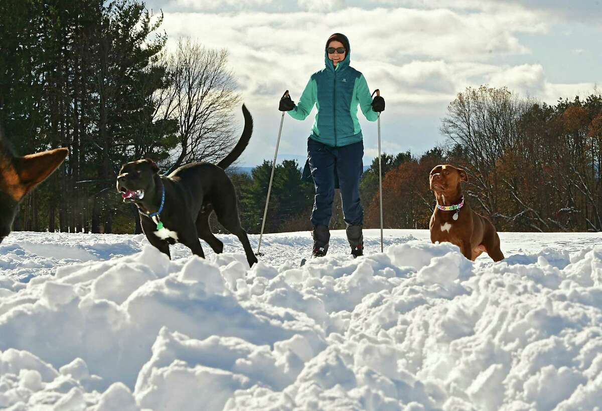 Rebecca Stetzer of Albany comes across some dogs being exercised at the end of her cross country ski routine at Capital Hills of Albany Golf Course on Thursday, Dec. 5, 2019 in Albany, N.Y. Better enjoy that snow this weekend. Meteorologist Jason Gough says it will warm up next week and the rising temperatures should put a dent in the snow pack. (Lori Van Buren/Times Union)