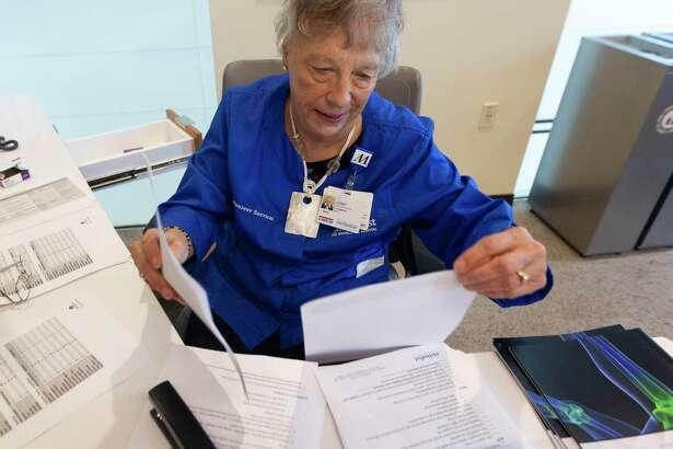 Volunteer Sheri Fitzgerald helps prepare information packets at Houston Methodist The Woodlands Hospital, Wednesday, Nov. 27, 2019.