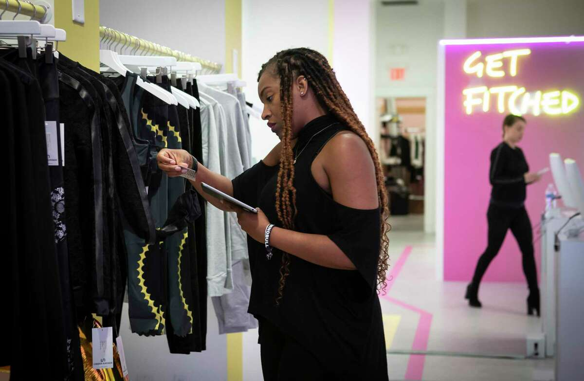 Assistant store manager Kandice Sayles looks at inventory inside the Fit Match pop-up at Baybrook Mall in Friendswood, Monday, Nov. 18, 2019.