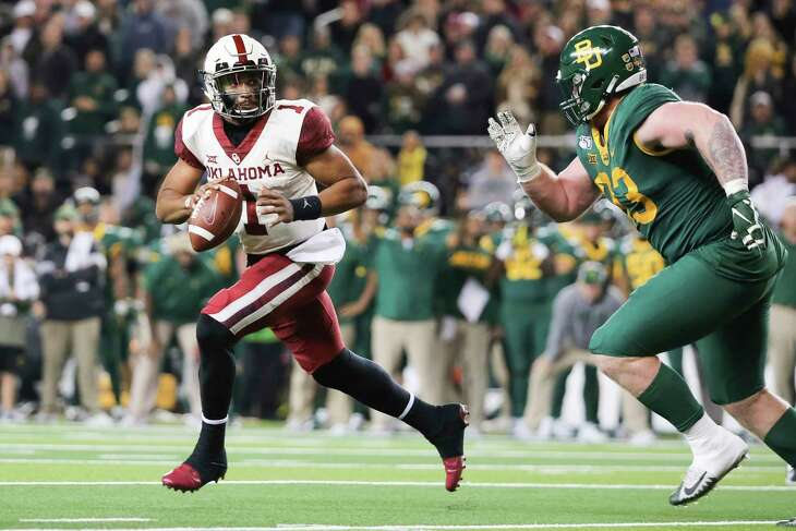 Oklahoma quarterback Jalen Hurts, left, rolls away from the pressure by Baylor defensive tackle James Lynch, right, during an NCAA college football game in Waco, Texas, Saturday, Nov. 16, 2019. Oklahoma won 34-31. (AP Photo/Ray Carlin)