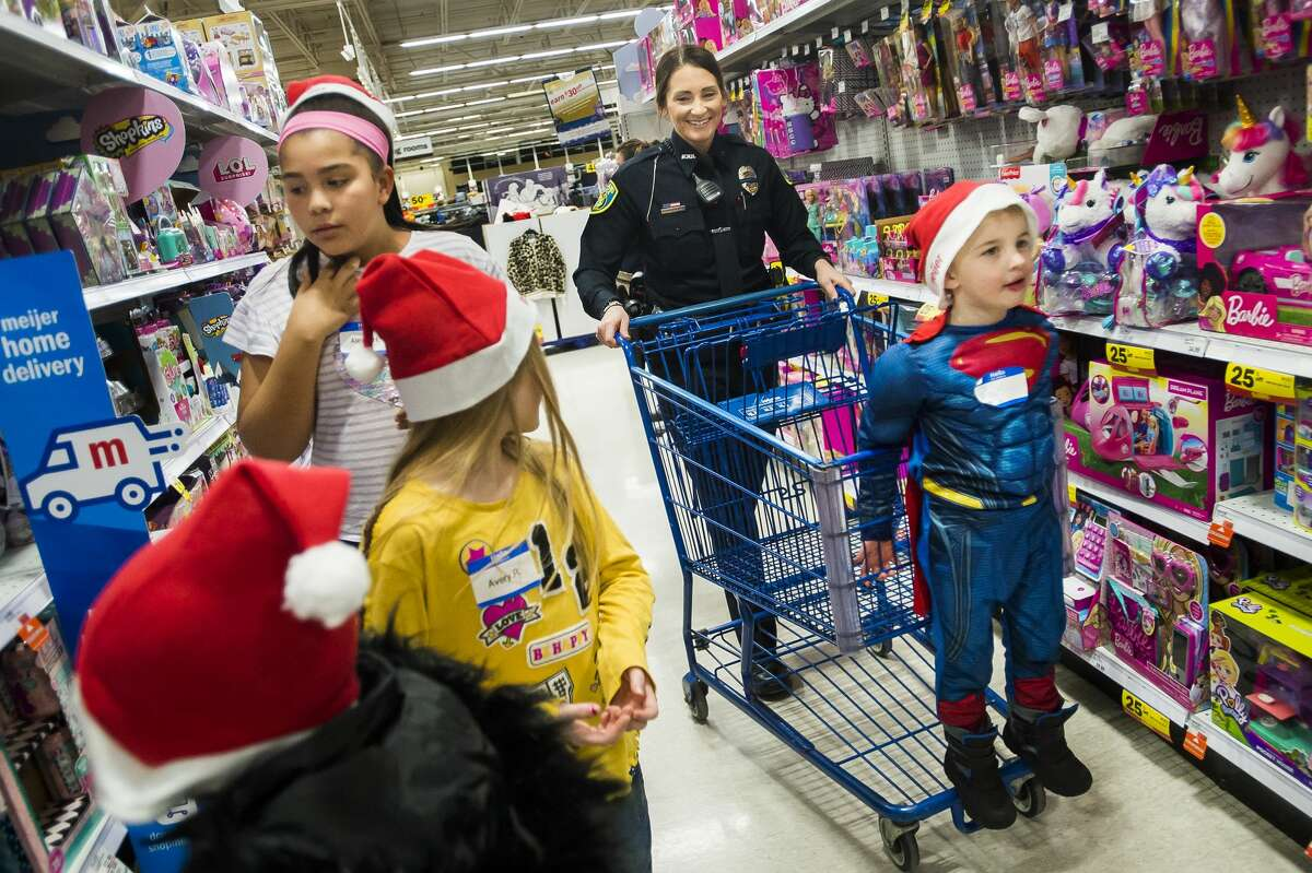 Matthew Gibson of Midland, 6, holds onto a shopping cart as Officer Haylee Porterfield of the Midland Police Department helps Matthew and three other kids pick out gifts for their family and friends during the annual Shop with a Hero event Tuesday, Dec. 3, 2019 at Meijer. (Katy Kildee/kkildee@mdn.net)