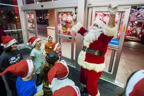 Children cheer as Santa arrives during the annual Shop with a Hero event Tuesday, Dec. 3, 2019 at Meijer. (Katy Kildee/kkildee@mdn.net)