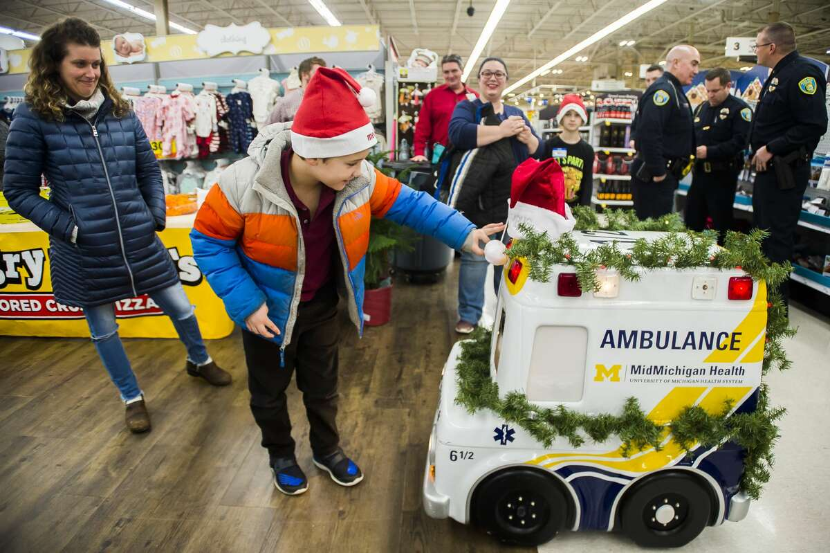 Issac Langbauer of Sanford, 10, reaches out to touch a remote-controlled miniature ambulance before participating in the annual Shop with a Hero event Tuesday, Dec. 3, 2019 at Meijer. (Katy Kildee/kkildee@mdn.net)