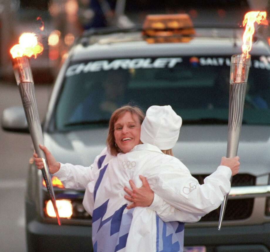 Donna Plewa-Allen of Katy, left, hugs Dana Walker, also of Katy, as they exchange the Olympic flame Dec. 10, 2001 along Post Oak. The pair were part of the 2002 Olympic Torch Relay, which carried the torch to Salt Lake City for the Winter Games. Photo: Smiley N. Pool, Staff / Houston Chronicle / Houston Chronicle