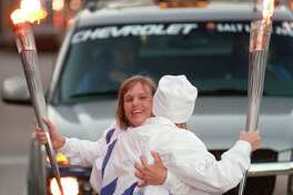 Donna Plewa-Allen of Katy, left, hugs Dana Walker, also of Katy, as they exchange the Olympic flame Dec. 10, 2001 along Post Oak. The pair were part of the 2002 Olympic Torch Relay, which will carry the torch to Salt Lake City for the Winter Games.