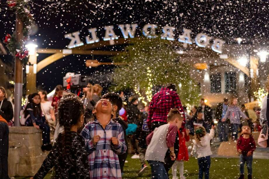 Children play in the falling snow during the fourth annual Light the Towne holiday celebration at Towne Lake Boardwalk on Dec. 4, 2019 in Cy-Fair. Photo: Courtesy Of Bryan Malloch