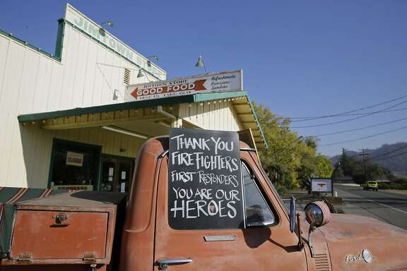 In this Wednesday, Nov. 6, 2019 photo, a sign thanking firefighters is displayed on the historic truck outside the Jimtown Store in Healdsburg, Calif. Tourism, which is usually booming amid the fall colors and mild temperatures, has taken a blow. Evacuations of nearby Healdsburg and Windsor, along with planned blackouts by the region's utility, PG&E, plus, the widespread misperception that the vineyards themselves burned have led to a rash of cancellations for hotel, restaurant and tasting-room reservations. (AP Photo/Eric Risberg)