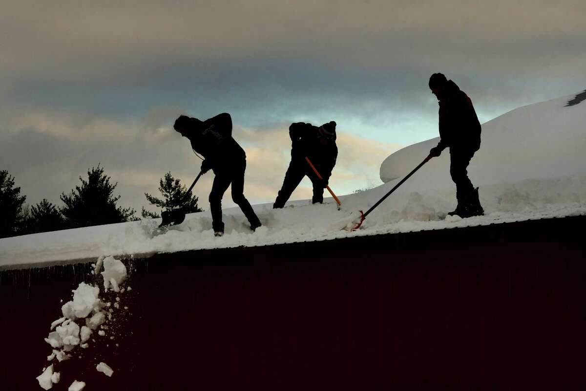 From left, Colby Robbins, Benjamin Sikoryak and Max Martin shovel snow off the roof of a barn at the Double M Western store on Thursday, Dec. 5, 2019 in Ballston Spa, N.Y. Max's parents are the owners and his friends were helping him with the roof. (Lori Van Buren/Times Union)