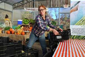 Lauren Henderson, harvest manager for Fort Hill Farm of New Milford, totes some crates at the Westport Farmer's Market on Saturday, Nov. 16, 2019, in Westport, Conn.