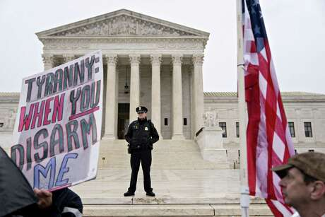 A U.S. Supreme Court police officer stands past gun-rights demonstrators outside the Supreme Court in Washington, D.C., U.S., on Monday, Dec. 2, 2019. Supreme Court justices today weighed tossing out a New York City firearms case, a move that would dash the hopes of gun-rights advocates seeking an expansion of Second Amendment protections. Photographer: Andrew Harrer/Bloomberg