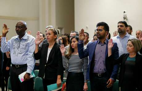 People raise their hands for the Oath of Allegiance during the United States Citizenship Naturalization Ceremony at City Hall in Houston. Processing time for citizenship applications has increased since 2016, leading to a backlog of about 80,000 citizenship cases in Texas.