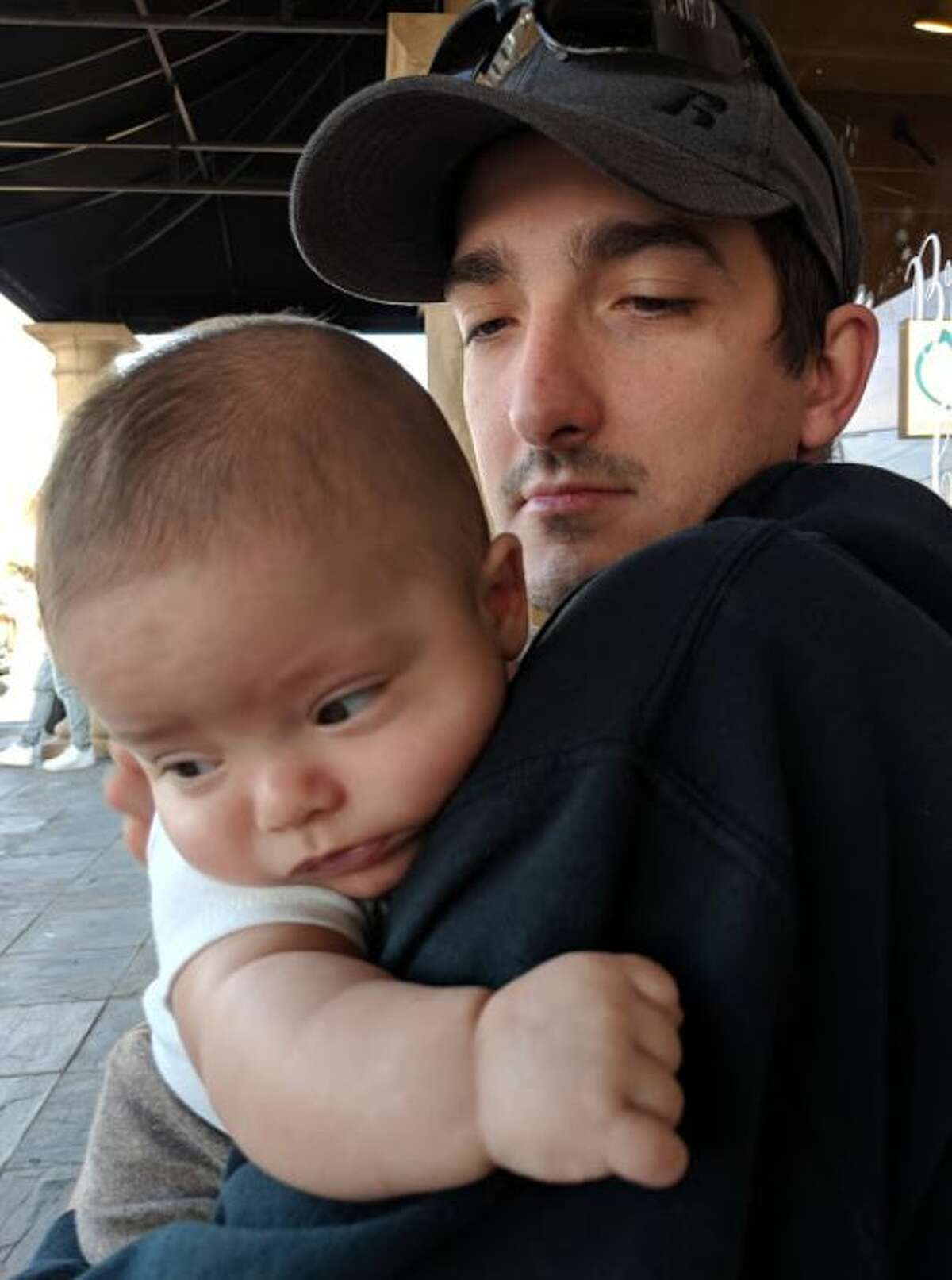 Kris Krischke and his 5-month-old son, Evrain, of Groves, wait as Kris' wife, Jena, deals with evacuation money at 250 N. Dowlen Road on Thursday.