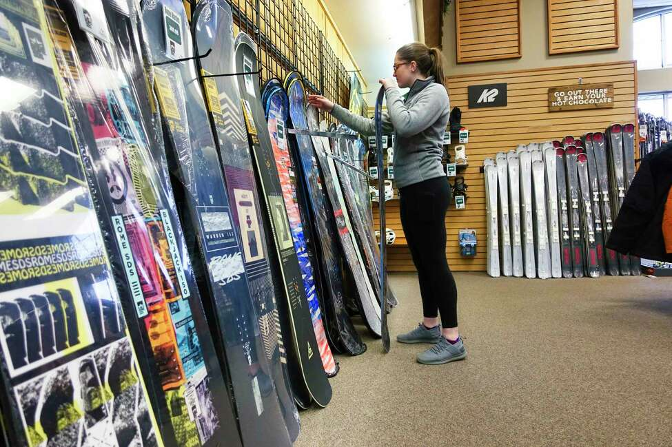 Colleen Heck, merchandise buyer at Alpin Haus, arranges snow boards in the store on Wednesday, Dec. 4, 2019, in Clifton Park, N.Y. (Paul Buckowski/Times Union)
