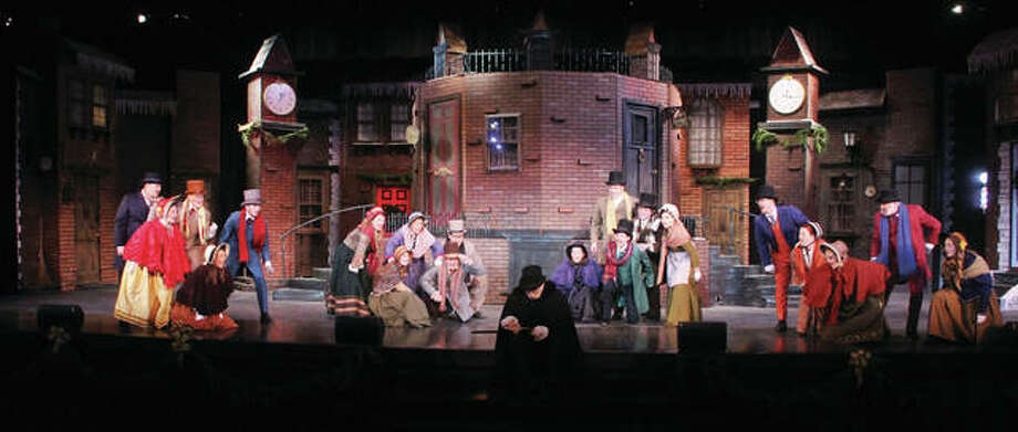 """Ebenezer Scrooge, played by Don Stratton, sits at the foot of the stage and contemplates his ledger book while Londoners sing about him in the Granite City High School production of """"A Christmas Carol."""" This is the 13th year of the production, which includes a cast and crew of more than 100 students and community members. The elaborate set includes a revolving stage, and several performers flying through the air. Public performances are Thursday through Saturday at 7 p.m. and 2 p.m. Sunday. Photo: Scott Cousins 