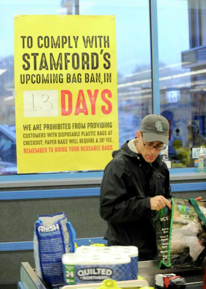 Mark Feiner of Greenwich bags his own groceries using recyclable bags after shopping April 20 in Stamford, where a ban on single-use plastic bags went into effect on May 3. Some cities enacted a ban before the statewide order on July 1. Photo: Matthew Brown / Hearst Connecticut Media / Stamford Advocate