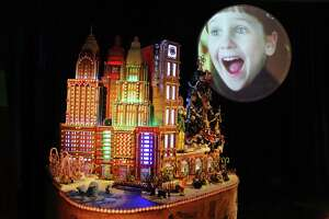 Scenes from various Christmas movies play on a circular screen above the 27th annual Gingerbread Village, on display at the Sheraton Grand Seattle until Jan. 1, 2020.  This year's village is themed Elves with each of the five elaborate gingerbread structures choosing a different elf motif.