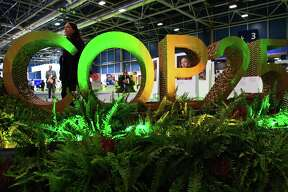 TOPSHOT - A visitors walks by the logo of the UN Climate Change Conference COP25 decorated with plants at the 'IFEMA - Feria de Madrid' exhibition centre, in Madrid, on December 2, 2019. - Spain's Socialist government offered to host this year's UN climate conference, known as COP25, from December 2 to December 13, 2019, after the event's original host Chile withdrew last month due to deadly riots over economic inequality. (Photo by GABRIEL BOUYS / AFP) (Photo by GABRIEL BOUYS/AFP via Getty Images)