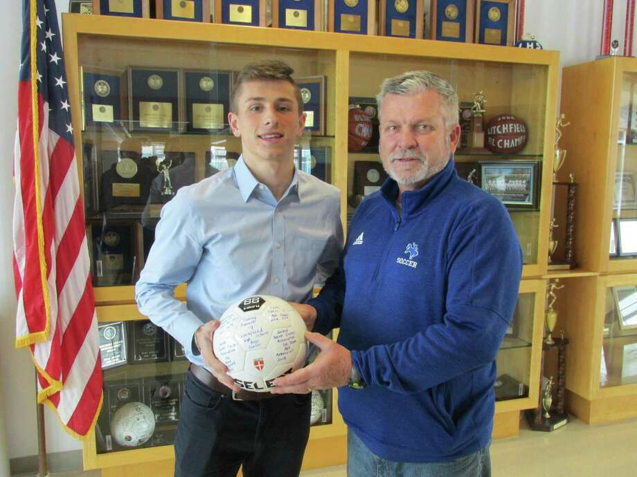 Litchfield soccer coach Rob Andrulis presented Timmy Donovan with a soccer ball commemorating Donovan's selection as a first-team U.S. Soccer Coaches Association All-American Wednesday afternoon at Litchfield High School. Photo: Peter Wallace / For Hearst Connecticut Media
