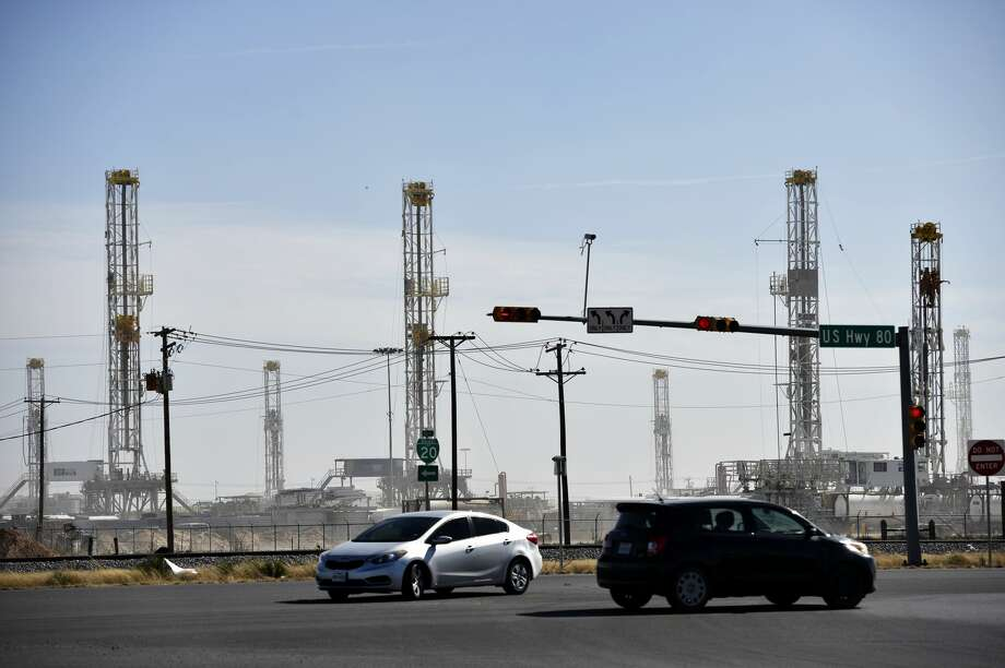 In this Feb. 18, 2019 file photo, vehicles navigate the intersection of Highway 80 and Faudree Road in Odessa, Texas in front of drilling rig parked at the HP Drilling yard. James Durbin/Reporter-Telegram Photo: James Durbin/Midland Reporter-Telegram