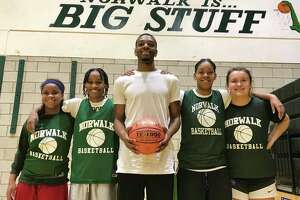 Norwalk seniors Carsyn Langhorn, Belinda Hunte, Anaijah Morgan and Grace Potochney stand with new Norwalk girls basketball coach Evan Kelley in the Norwalk gym on Dec. 5, 2019 in Norwalk, Conn.