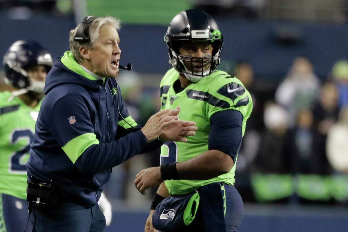 Seattle Seahawks head coach Pete Carroll, left, talks with quarterback Russell Wilson during the first half of an NFL football game against the Minnesota Vikings, Monday, Dec. 2, 2019, in Seattle.