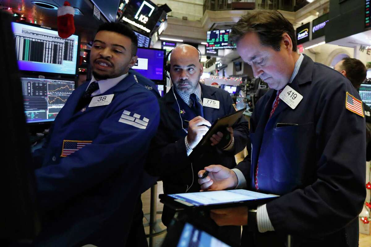 Specialist Christopher Riggs, left, works with traders Fred DeMarco, center and Philip Powers on the floor of the New York Stock Exchange, Thursday, Dec. 5, 2019. Stocks are opening slightly higher on Wall Street led by technology companies and banks. (AP Photo/Richard Drew)